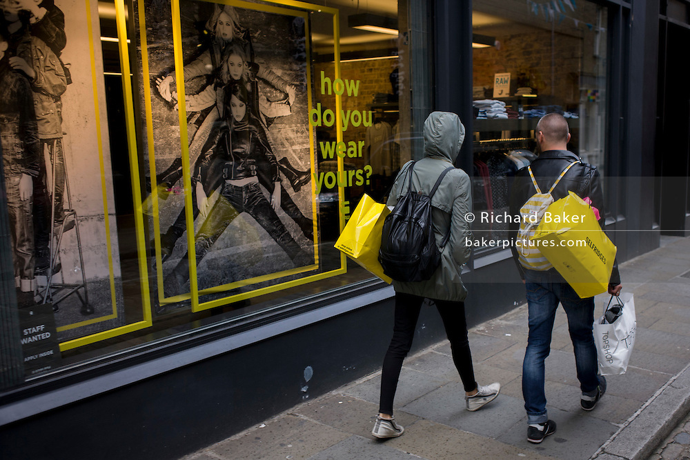 Two young shoppers carrying yellow Selfridges bags walk past a yellow rectangle theme near Seven Dials in central London.