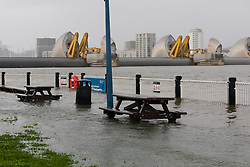 © Licensed to London News Pictures. 10/02/2020. London, UK. Benches are seen underwater during flooding at the Thames Barrier in London which is seen closed this afternoon at high tide to protect the capital from flooding during Storm Ciara. The Thames Barrier prevents the floodplain of most of Greater London from being flooded by exceptionally high tides and storm surges.  Photo credit: Vickie Flores/LNP