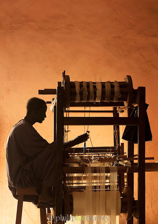 An artisanal weaver works with his loom in a market in Bamako, Mali