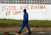 A man walks past some grafiti in Bulawayo, Zimbabwe the day after the country went to the election polls. It reads: Good bye Mugabe, RIP Zanu PF.
