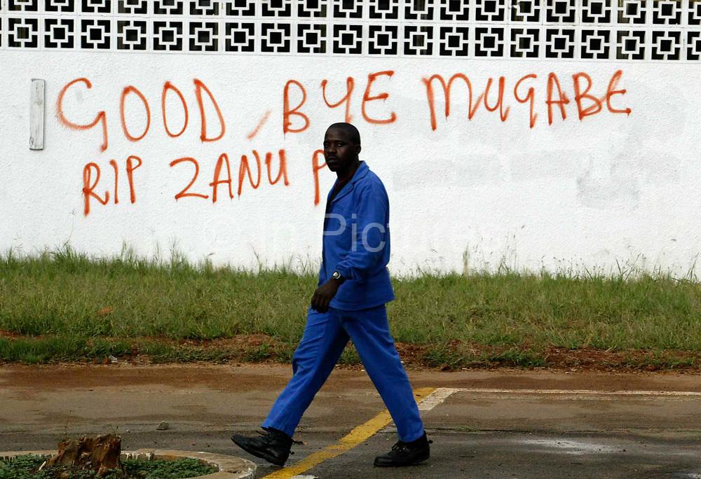 A man walks past some grafiti in Bulawayo, Zimbabwe the day after the country went to the election polls. It reads: Good bye Mugabe, RIP Zanu PF.