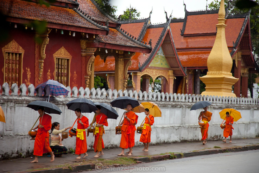 """Luang Prabang, Laos. Every morning at dawn, Buddhist monks walk down the streets collecting food alms from devout, kneeling Buddhists, and some tourists. They then return to their temples (also known as """"wats"""") and eat together. This procession is called Tak Bat, or Making Merit."""
