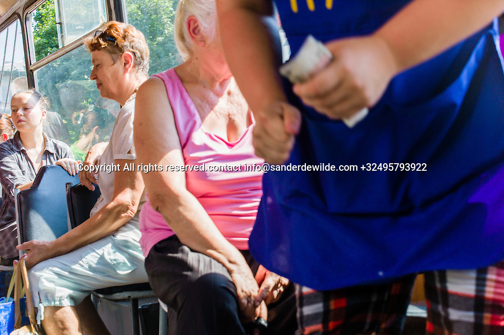 20150829  Moldova, Transnistria,Pridnestrovian Moldavian Republic (PMR) Tiraspol. Trolleybus filled with people, sitting and standing. Trolley buses have a fixed price, and a Konduktor passes by to sell tickets, money in her hand wearing a blue apron.