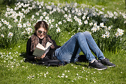 © Licensed to London News Pictures. 26/03/2017. LONDON, UK. A woman relaxes with a book during sunny spring weather in St James's Park, London this lunchtime. Today is the first day of British Summer Time (BST). Photo credit: Vickie Flores/LNP