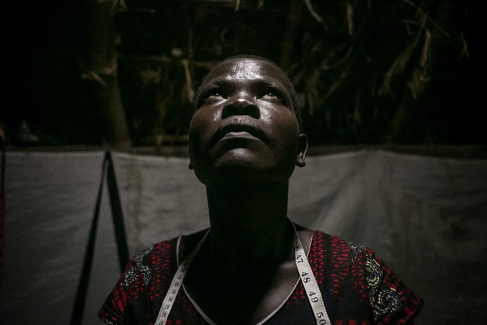 Anek Grace, 30, a former girl soldier and sex slave, looks at the solar lamp inside her hut in Gulu. She was abducted at eight in Palaro village when a team of 100 LRA soldiers attacked in 1995. She was too young to be assigned to a husband, so LRA waited until she became ten years old. She was raped by lieutenant as he put the pistol on the bed and tied up her hands. She stayed in LRA for 12 years and gave birth to a daughter in 2005. Now she makes bags at an NGO, WEND Africa, and does sawing during her breaks.