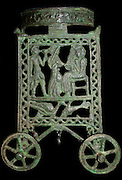 Bronze wheeled stand with an animal frieze on the ring and figures in the side panels, made in Cyprus 13th 12th Century BC.