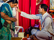 "23 SEPTEMBER 2018 - BANGKOK, THAILAND:  A Hindu priest gives a woman a ""talika"" at the Ganesha Festival at Wat Dan in Bangkok. Ganesha Chaturthi also known as Vinayaka Chaturthi, is the Hindu festival celebrated on the day of the re-birth of Lord Ganesha, the son of Shiva and Parvati. The festival, also known as Ganeshotsav (""festival of Ganesha"") is observed in the Hindu calendar month of Bhaadrapada, starting on the the fourth day of the waxing moon. The festival lasts for 10 days, ending on the fourteenth day of the waxing moon. Outside India, it is celebrated widely in Nepal and by Hindus in the United States, Canada, Mauritius, Singapore, Thailand, Cambodia, and Burma.   PHOTO BY JACK KURTZ"