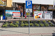 A Polish mother and her child walk past advertising signs, on 21st September 2019, in Szczawnica, Malopolska, Poland.