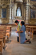 27 APRIL 2005 - SAN CRISTOBAL DE LAS CASAS, CHIAPAS, MEXICO:A family prays in Templo de Santo Domingo, San Cristobal de las Casas, Chiapas. San Cristobal is the center of the Chiapas highlands and an important indigenous community. Fear of political violence in the area has diminished in recent years and the tourism industry has rebounded as a result.  PHOTO BY JACK KURTZ