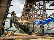 17 SEPTEMBER 2014 - SANGKHLA BURI, KANCHANABURI, THAILAND:  A Thai soldier relaxes at the base of the Mon Bridge during the bridge repair. The 2800 foot long (850 meters) Saphan Mon (Mon Bridge) spans the Song Kalia River. It is reportedly second longest wooden bridge in the world. The bridge was severely damaged during heavy rainfall in July 2013 when its 230 foot middle section  (70 meters) collapsed during flooding. Officially known as Uttamanusorn Bridge, the bridge has been used by people in Sangkhla Buri (also known as Sangkhlaburi) for 20 years. The bridge was was conceived by Luang Pho Uttama, the late abbot of of Wat Wang Wiwekaram, and was built by hand by Mon refugees from Myanmar (then Burma). The wooden bridge is one of the leading tourist attractions in Kanchanaburi province. The loss of the bridge has hurt the economy of the Mon community opposite Sangkhla Buri. The repair has taken far longer than expected. Thai Prime Minister General Prayuth Chan-ocha ordered an engineer unit of the Royal Thai Army to help the local Mon population repair the bridge. Local people said they hope the bridge is repaired by the end November, which is when the tourist season starts.   PHOTO BY JACK KURTZ