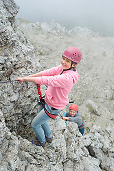 Brother sister climbing rock face mountains rope