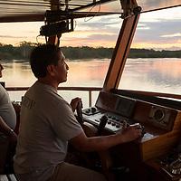 Crew members steer the Delfin II ship at sunset on the Marañon River. Pacaya Samiria National Reserve, Upper Amazon, Peru.