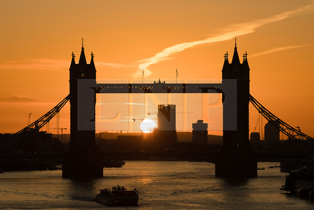 © Licensed to London News Pictures. 30/10/2017. LONDON, UK.  Sunrise behind Tower Bridge on the River Thames as a commuter boat travels along.  London has woken to cold and clear weather this morning. Photo credit: Vickie Flores/LNP