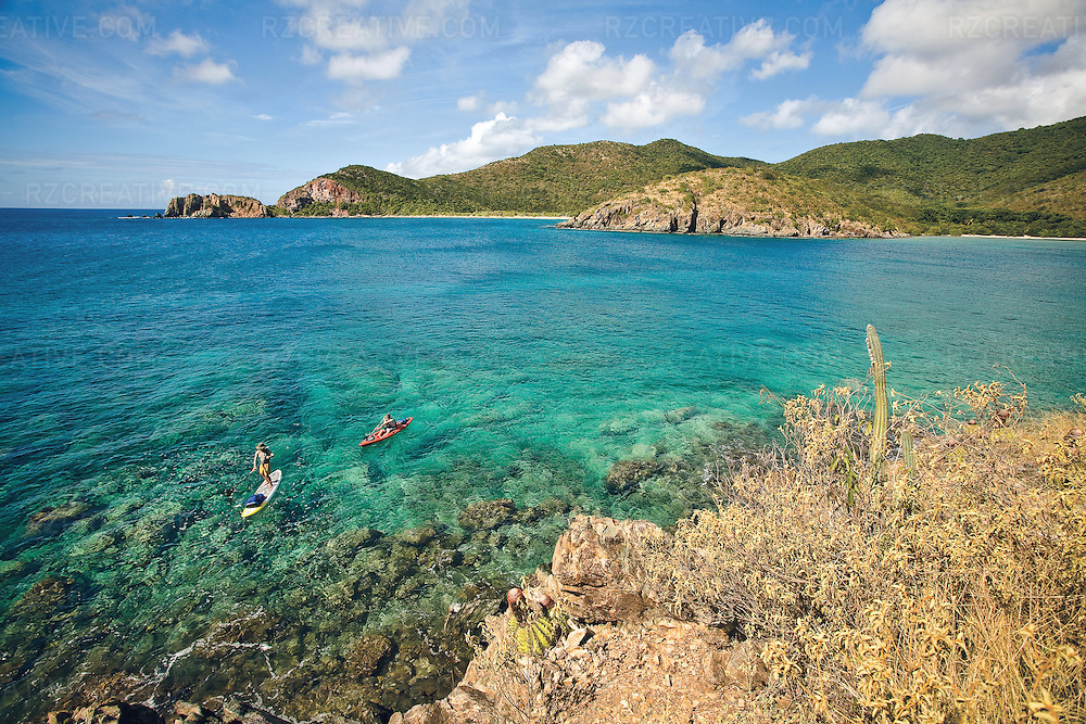 Two men paddle a sit-on-top kayak and standup paddleboard at Lameshur Bay on the island of St. John, part of the U.S. Virgin Islands.