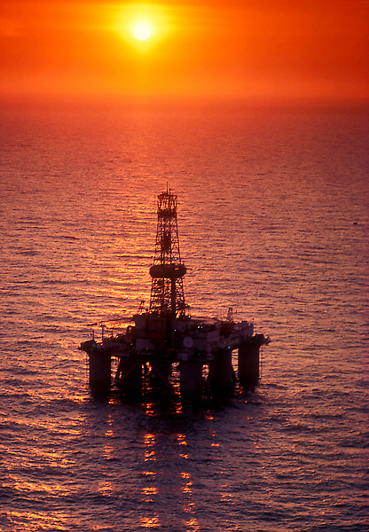 An semi-submersible offshore oil drilling rig at sunset.