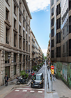 The streets of Barcelona are lined with historical buildings and narrow sidewalks.