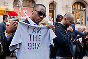 "A man holds a stencilled shirt that reads ""I am the 99%""."