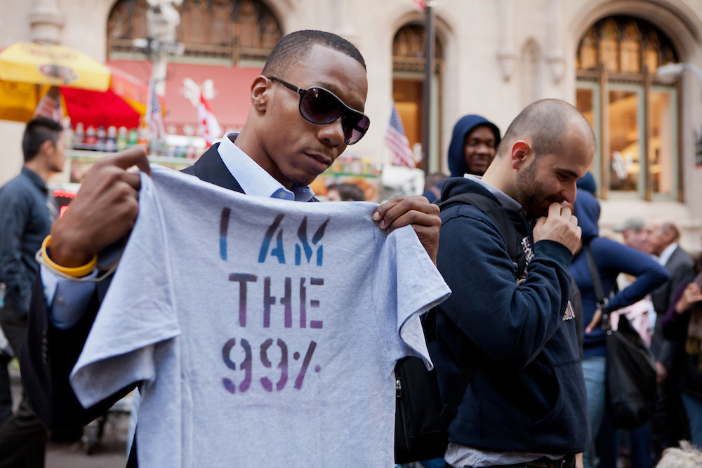 """A man holds a stencilled shirt that reads """"I am the 99%""""."""