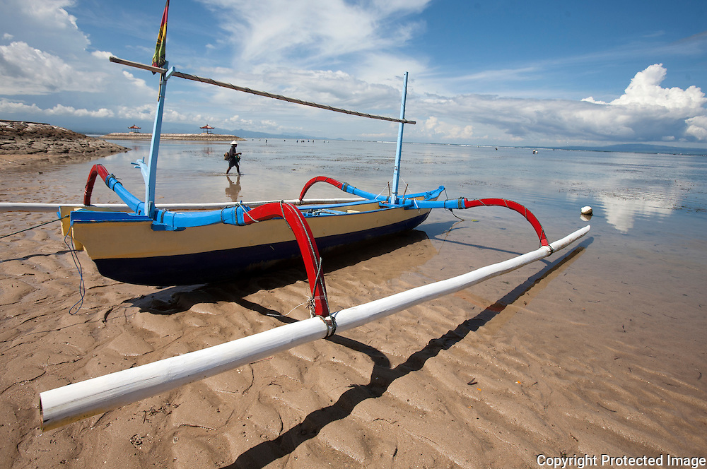 A fisherman heads into the water in Sanur on the Island of Bali in Indonesia.