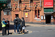 Group of Chinese men havng a meeting wearing surgical face masks on a street corner in an otherwise deserted Chinese Quarter on 24th April 2020 in Birmingham, England, United Kingdom. Coronavirus or Covid-19 is a new respiratory illness that has not previously been seen in humans. While much or Europe has been placed into lockdown, the UK government has extended stringent rules as part of their long term strategy, and in particular social distancing.