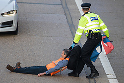 Ockham, UK. 21st September, 2021. A Surrey Police officer drags an Insulate Britain climate activist from the anticlockwise carriageway of the M25 between Junctions 9 and 10. Activists briefly halted traffic on both carriageways of the motorway as part of a campaign intended to push the UK government to make significant legislative change to start lowering emissions.