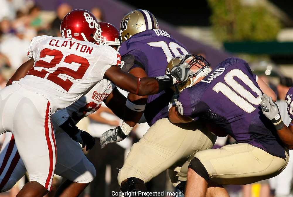 Washington quarterback Jake Locker is pulled down by his helmet by Oklahoma's Keenan Clayton during the second quarter of an NCAA college football game in Seattle. Clayton was called for a face mask penalty. (AP Photo/John Froschauer)