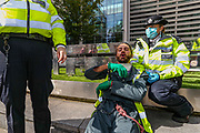 An Extinction Rebellion climber who tried to occupy one of the trees outside Home Office in Marsham Street in London is arrested and handcuffed by the Police on Friday, Sept 4, 2020. <br /> Marsham street remains both ways closed by the police. There are other Extinction Rebellion protests ongoing in London. Environmental nonviolent activists group Extinction Rebellion enters its 4th day of continuous ten days protests to disrupt political institutions throughout peaceful actions swarming central London into a standoff, demanding that central government obeys and delivers Climate Emergency bill. (VXP Photo/ Vudi Xhymshiti)