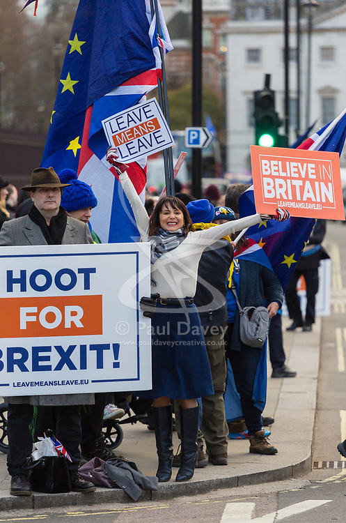 Pro-Leave protester Lydia, originally an immigrant from Peru and now a British citizen tries to attract hoots from passing cars outside the Houses of Parliament in London. London, January 14 2019.