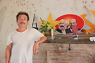 A vietnamese man poses beside a picture of Karl Marx and Lenin, Vietnam, Southeast Asia