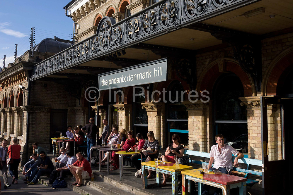 In the late afternoon on a warm summer's day, drinkers enjoy a pint or two outside The Phoenix pub at Denmark Hill station, Camberwell, South London. Seated at tables and on benches, the friends and colleagues relax in the warm sunshine outside this Victorian station, built in 1865. Its design is in the Italianate style, with an extremely decorative frontage. After a fire in 1980 the building was renovated and restored. The project included the addition of the public house, initially called the Phoenix and Firkin to commemorate the fire, then called O'Neills and now known as the Phoenix. A Civic Trust award was given to the building in 1986.