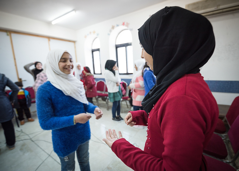 16 February 2020, Irbid, Jordan: Two girls play a game of 'mirroring', whereby one of them leads and the other has to mimmick what she is doing. This, during a psychosocial support session for Syrian refugee children and Jordanian host communities, led by the Lutheran World Federation at the Islamic Centre in Al-Mazar.