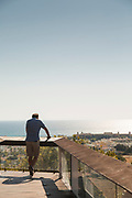 Man standing on balcony looking at old town, Paphos, Cyprus
