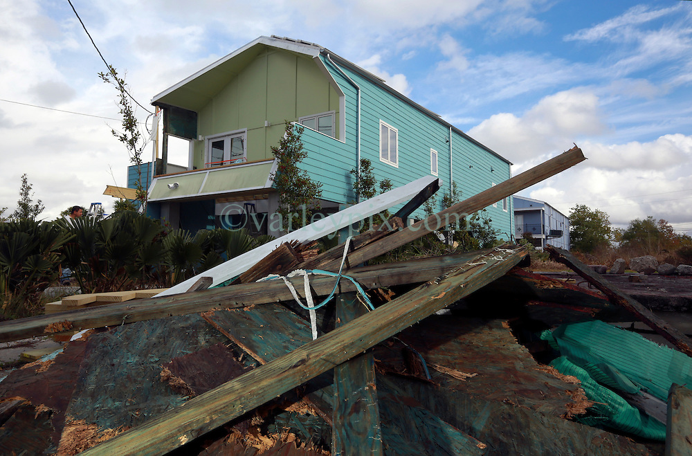 03 December 2013. Lower 9th Ward, New Orleans, Louisiana. <br /> A pile of rotted wood sits in front of a Brad Pitt 'Make it Right' home on Tennessee Street. Contractors are busy replacing the rotten stairs and front deck of  the recently built home.<br /> Photo; Charlie Varley