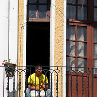 South America, Ecuador, Quito. Local resident plays the bongo drums on his balcony in Quito.