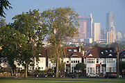 Through a gap of 100 year-old ash trees, Edwardian period homes bordering Ruskin Park in south London with residential high-rises at the distant Nine Elms development in Battersea, on 16th September 2021, in London, England.