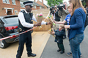 © Licensed to London News Pictures. 23/04/2014. New Malden, UK. People arrive with towers. The scene in New Malden where a woman has been arrested after the discovery of three bodies of children in a house overnight. Photo credit : Stephen Simpson/LNP