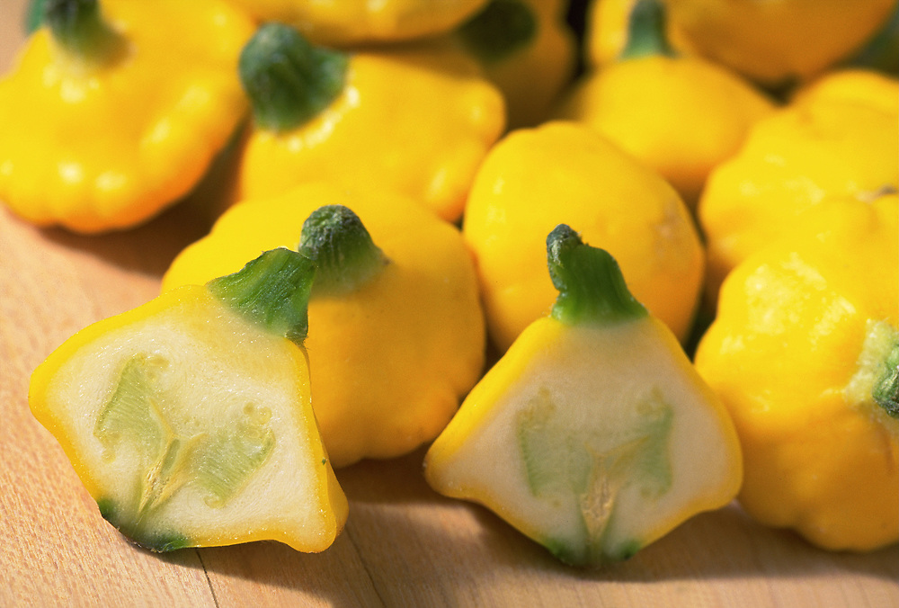 Close up selective focus photograph of some Yellow Pattypan Squash on a butcher block table with one cut in half