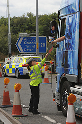 © Licensed to London News Pictures. 28/07/2015<br /> Operation Stack chaos at Junction 8 of the M20 in Kent. Police in control of the M20 a Kent police officer checking papers for lorry pass.<br /> <br /> Operation stack is back on the M20 in Kent.<br /> Just days after Operation Stack was taken off the M20, it was brought back in the early hours of this morning.<br /> The authorities are blaming a heavy volume of traffic heading towards the Port of Dover and Eurotunnel and the continued disruption in Calais.<br /> The coast-bound carriageway between junctions 8 and 9 is closed to allow lorries to park, but the slip roads at junctions 9, 10 and 12 and 13 have also been shut. <br /> <br /> (Byline:Grant Falvey/LNP)