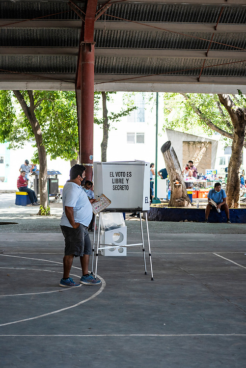 Tulum, Mexico - June 6, 2021: A man steps up to the voting booth at a precinct in Tulum during Mexico's mid-term elections.