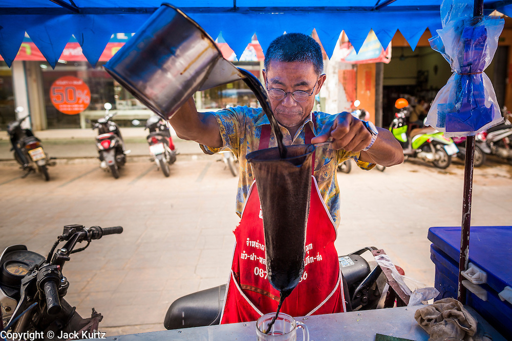 23 MAY 2013 - MAE SOT, TAK, THAILAND:  A Thai iced coffee vendor at work in the Burmese market in Mae Sot. Fifty years of political turmoil in Burma (Myanmar) has led millions of Burmese to leave their country. Many have settled in neighboring Thailand. Mae Sot, on the Mae Nam Moei (Moei River) is the center of the Burmese emigre community in central western Thailand. There are hundreds of thousands of Burmese refugees and migrants in the area. Many live a shadowy existence without papers and without recourse if they cross Thai authorities. The Burmese have their own schools and hospitals (with funding provided by NGOs). Burmese restaurants and tea houses are common in the area.    PHOTO BY JACK KURTZ