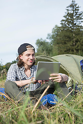 Teenage boy using digital tablet in front of camp tent, Bavaria, Germany