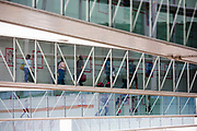 "Airline passengers make their way along jetties from their newly-arrived aircraft, towards the arrivals concourse in Heathrow Airport's Terminal 5. We see four lines of jetties that are owned by the airport operator, used by British Airways and sponsored by HSBC. Air travellers walk briskly after their long-haul flight either carrying light carry-on bags or towing small cases on wheels. At a cost of £4.3 billion, Terminal 5 has the capacity to serve around 30 million passengers a year. From writer Alain de Botton's book project ""A Week at the Airport: A Heathrow Diary"" (2009)."