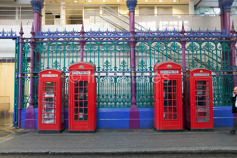 Four red telephone boxes of different sizes situated under cover in Smithfields meat market in London, UK. This iconic design is now just an object as telecomunication via mobile phone has made the public call box obsolete.