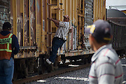 """Central american migrants wait for the train in Tultitlán, Estado de México, under the bridge Independencia while they are observed by security personnel after the migrants shelter  """"San Juan Diego Cuauhtlatoatzin"""" was closed in Lecheria, Estado de México on July 9th, 2012. (Photo: Prometeo Lucero)"""