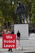 Pro Brexit protester with a We Voted Leave placard beside the statue of Winston Churchill in Parliament Square in Westminster on 2nd October 2019 in London, England, United Kingdom.