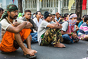 "11 MAY 2013 - BANGKOK, THAILAND:   Farmers sit in the road in front of Government House. Several hundred small scale family farmers camped out ""Government House"" (the office of the Prime Minister) in Bangkok to Thai Prime Minister Yingluck Shinawatra to deliver on her promises to improve the situation of family farmers. The People's Movement for a Just Society (P-move) is a network organization which aims strengthen the voices of different, but related causes working to bring justice for marginalized groups in Thailand, including land rights for small-scale farmers, citizenship for stateless persons, fair compensation for communities forced to relocate to accommodate large scale state projects, and housing solutions for urban slum dwellers, among others.   PHOTO BY JACK KURTZ"