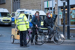 © Licensed to London News Pictures; 25/01/2021; Bristol, UK. Colston Four at court. A man playing music with a sound system on a bicycle trailer outside court is arrested by police. Defendants Rhian Graham, 29, Milo Ponsford, 25, Jake Skuse, 32, and Sage Willoughby, 21, are due before Bristol Magistrates' Court for their first hearing today. They have been charged with criminal damage in connection with damage to the statue of slave trader Edward Colston which was pulled down during a Black Lives Matter protest on June 7 2020 and then thrown into Bristol Harbour. Police launched an appeal to trace suspects after the event and ten people were located. Six people accepted a caution while four were referred to the CPS. The statue was later retrieved by Bristol City Council who say that the damage is costed at £3,750. Police have warned anyone planning to protest at the court hearing that they will be breaking the lockdown laws which prohibit public gatherings of more than two people to combat the Covid-19 coronavirus pandemic. Photo credit: Simon Chapman/LNP.