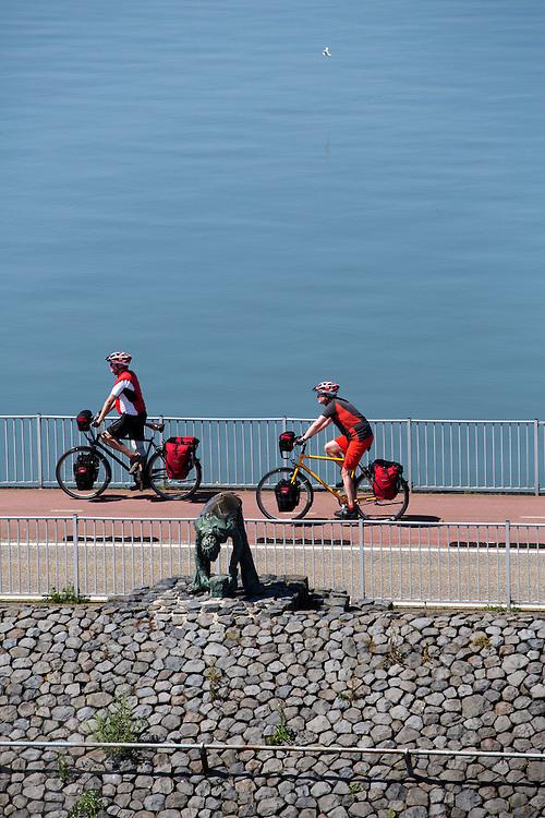Fietsers rijden over de Afsluitdijk. In 1932 werd de opening tussen de Waddenzee en de toenmalige Zuiderzee gesloten. Nu is het een belangrijke verkeersader tussen Friesland en Noord-Holland en scheidt het de Waddenzee met het IJsselmeer.<br /> <br /> Cyclists are riding on the Afsluitdijk. In 1932, the gap between the Wadden Sea and the former Zuiderzee closed by the Afsluitdijk. Now it is a major thoroughfare between Friesland and North Holland and it separates the Wadden Sea from the IJsselmeer.