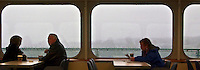 Washington State Ferries passengers sit and watch the gloomy rain as they cross Puget Sound, Washington, USA panorama