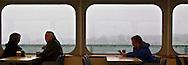 Washington State Ferries passengers sit and watch the gloomy rain as they cross Puget Sound, Washington, USA panorama